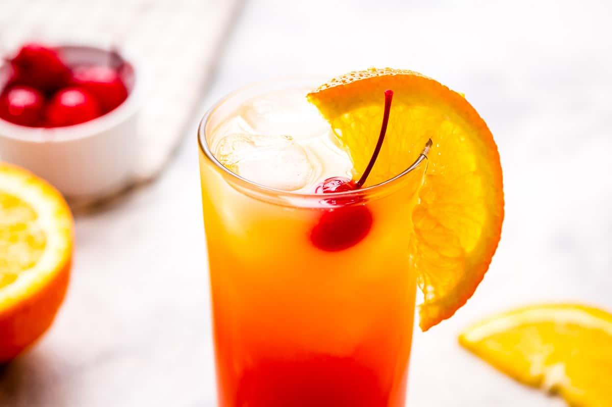 Tequila Sunrise with a maraschino cheery and orange slice garnish