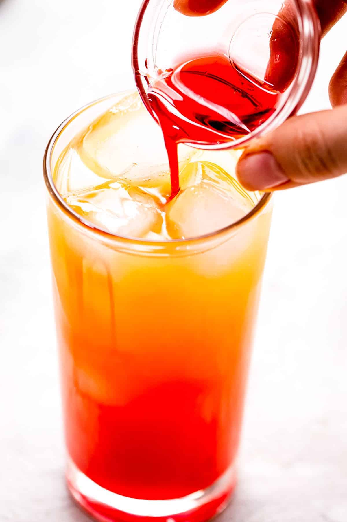 Hand pouring maraschino cherry juice into a high ball glass with orange juice