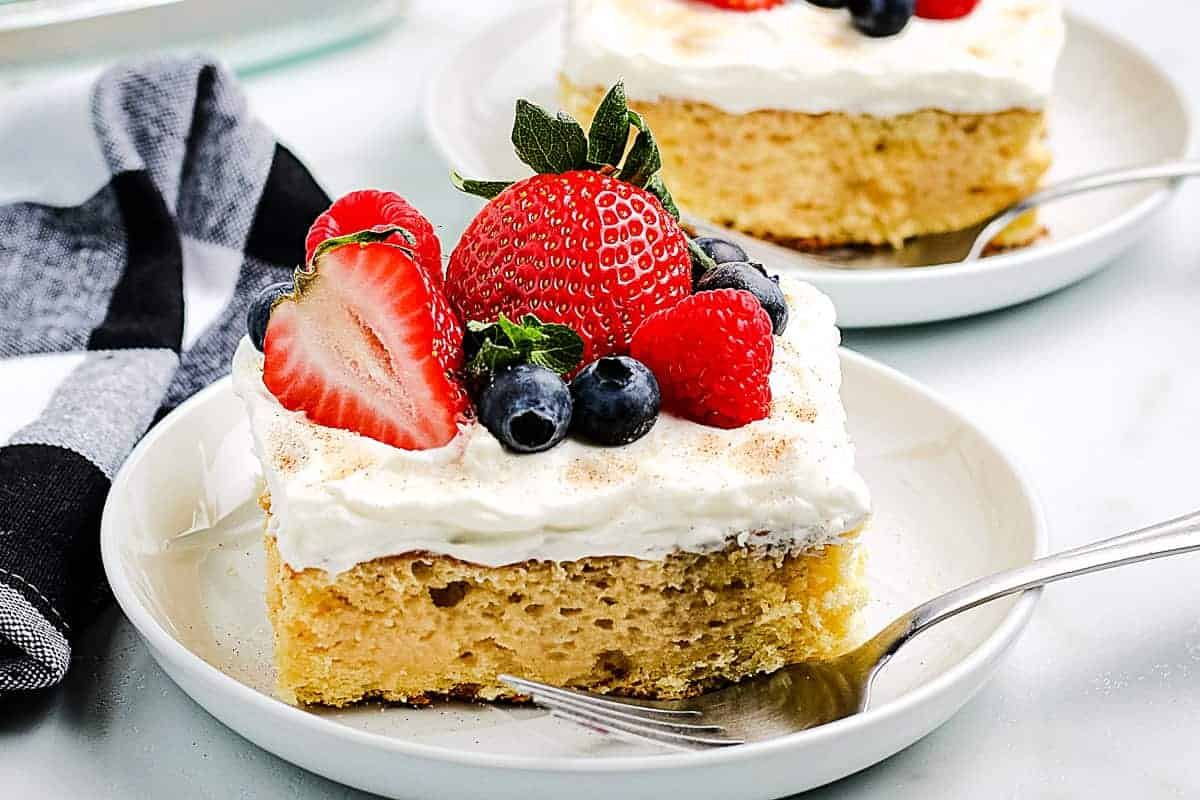 Tres Leche Cake on a white plate with fork