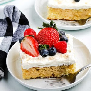White plate with a piece of tres leche cake topped with fresh fruit.