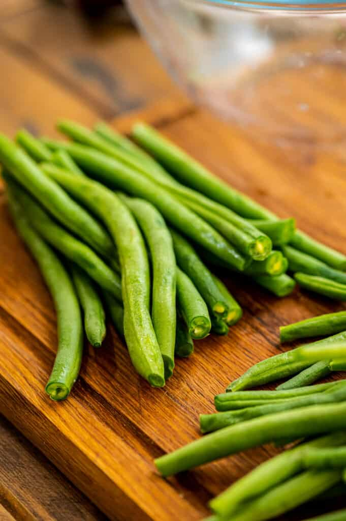 Trimmed Green Beans on a wood cutting board