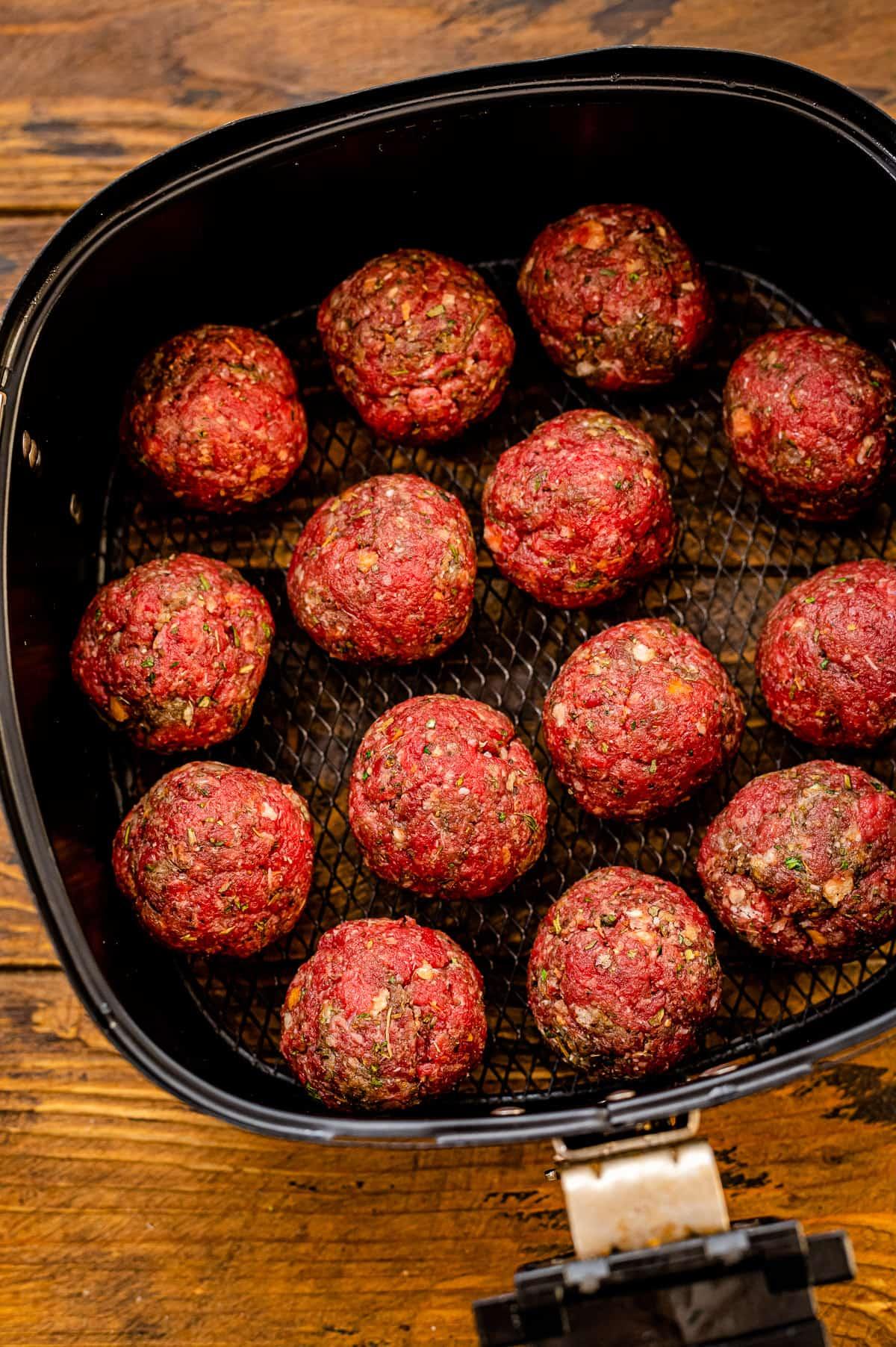 Air Fryer meatballs in air fryer basket before cooking