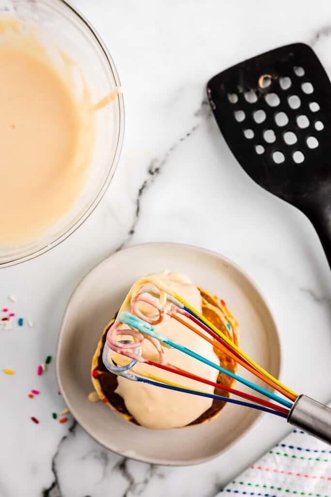 Overhead image of putting vanilla frosting on funfetti pancakes
