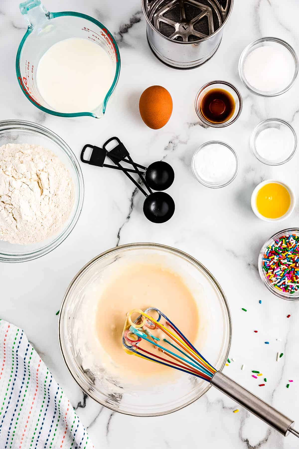Ingredients in glass bowl mixed up to make frosting for funfetti pancakes