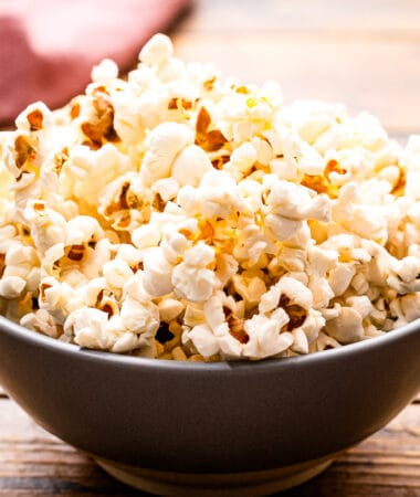 A bowl of popcorn sitting on a wooden background