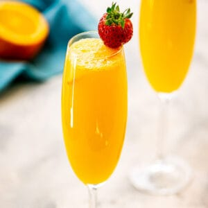 Close up image of a Mimosa with a strawberry garnish