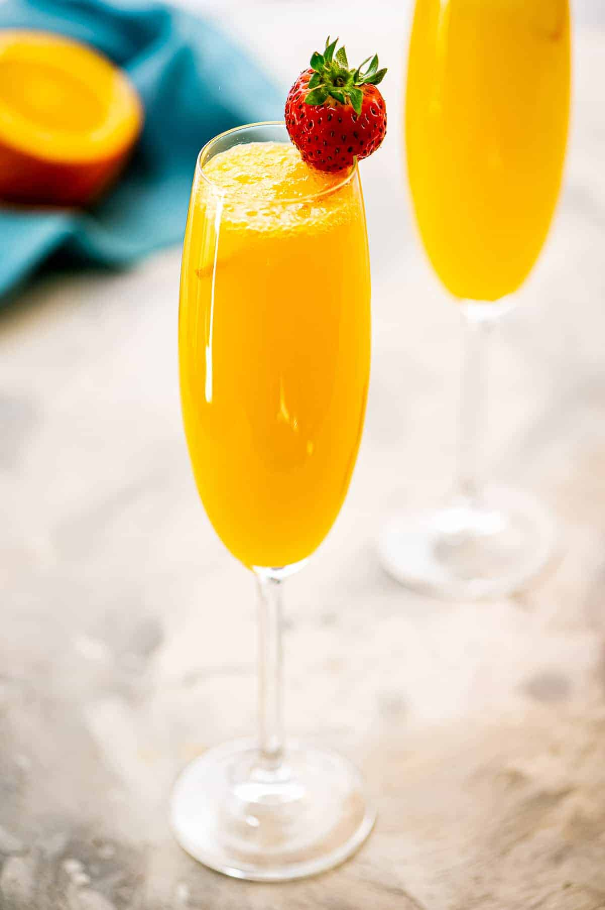 Champagne flute with a Mimosa in it and strawberry garnish