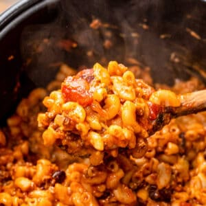 Spoon with Chili Mac over a pressure cooker