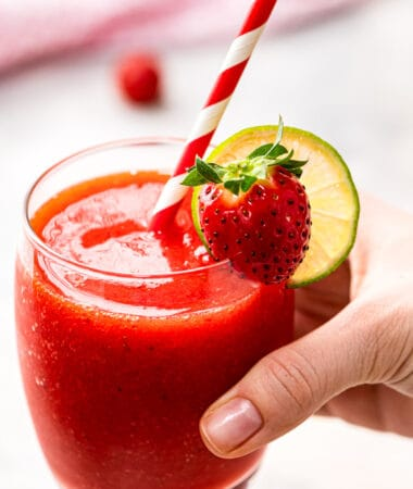 Hand holding a glass with frozen strawberry daquiri