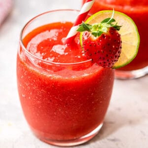Close up of a glass of Frozen Strawberry Daquiri garnished with lime wheel and strawberry