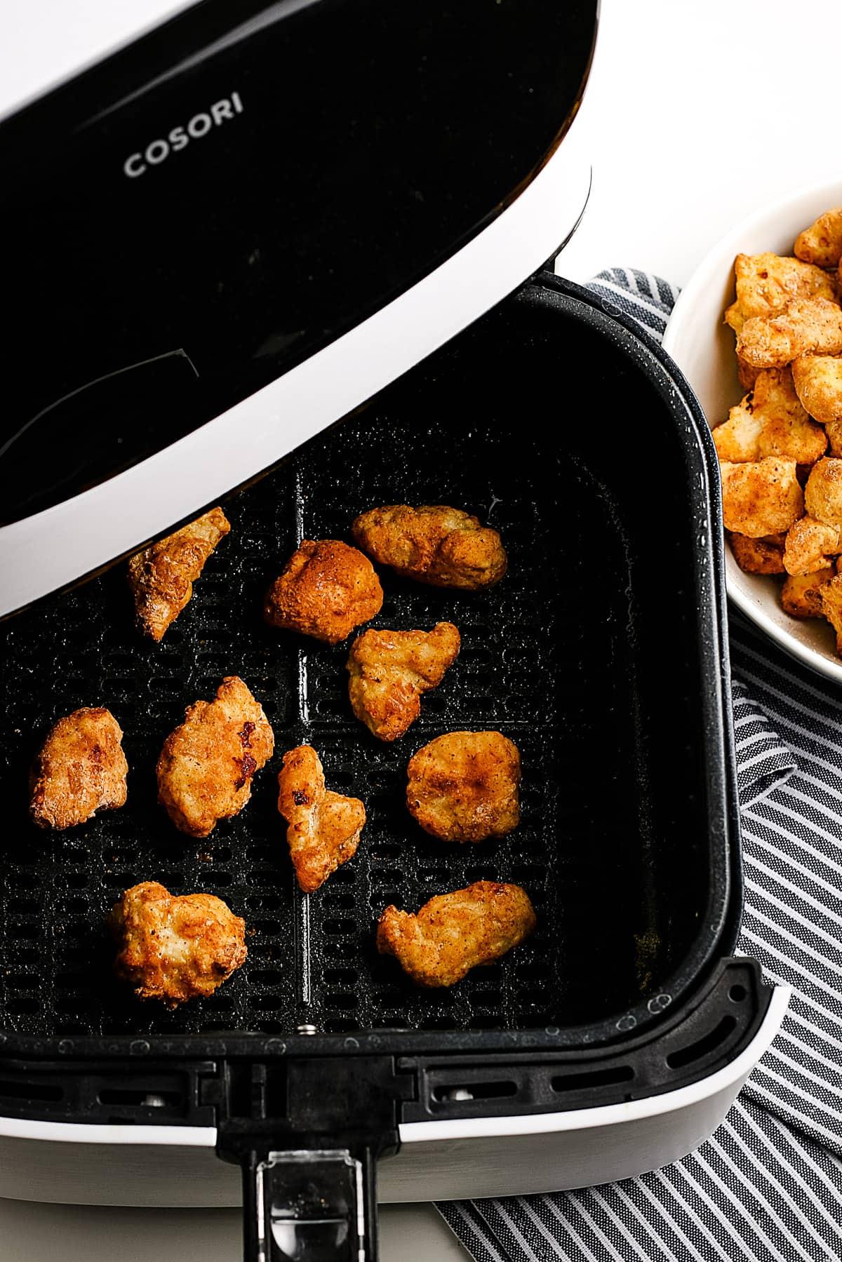 Air Fryer Basket with popcorn chicken in it