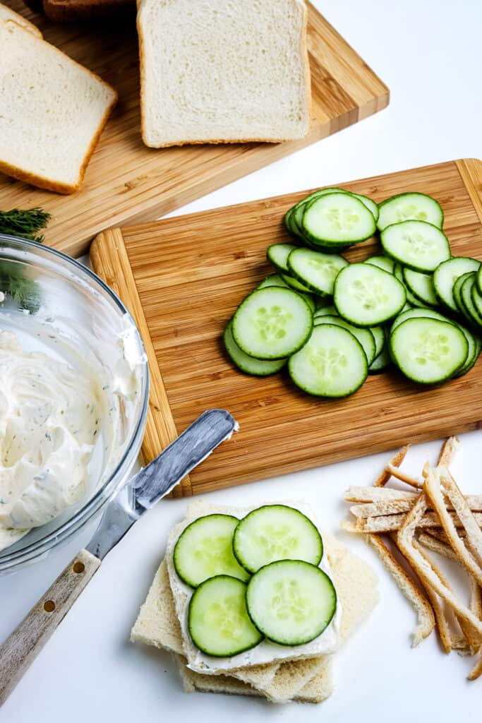 Bread slice topped with dill cream cheese spread and sliced cucumbers