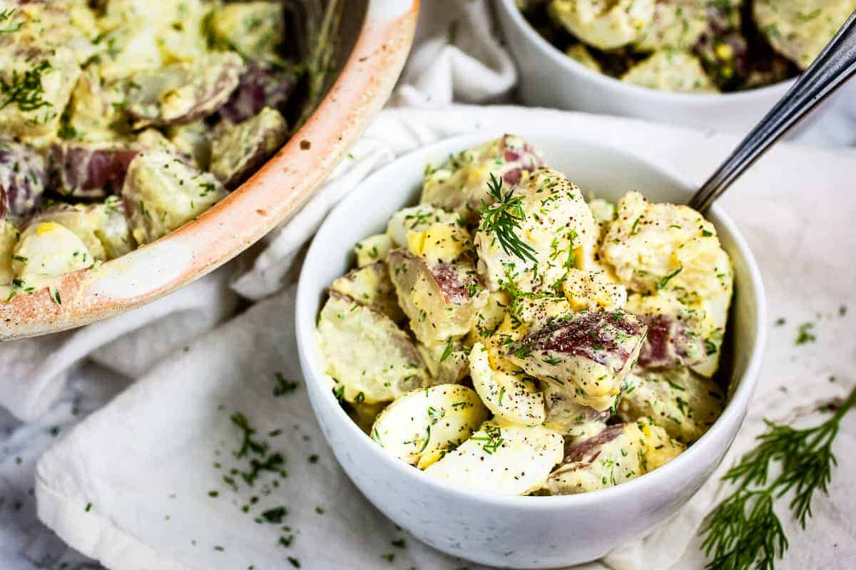 Small white bowl with dill potato salad