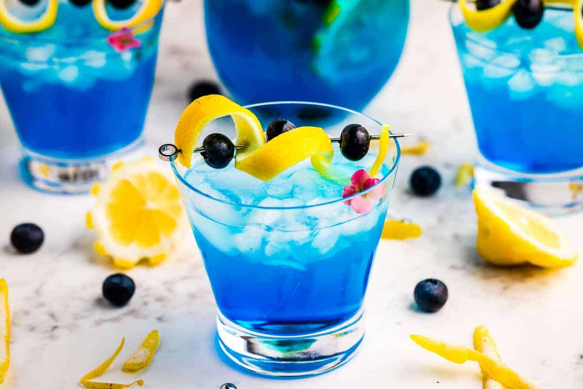 Ocean Breeze Cocktail in small glass garnish with lemon peel and blueberries