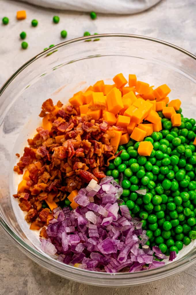 Ingredients for pea salad before mixing in glass bowl