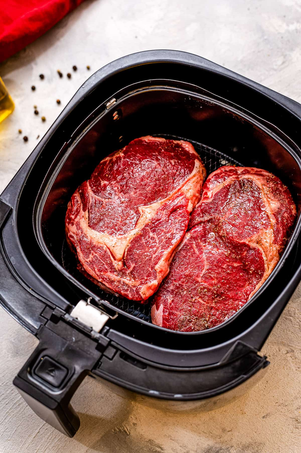 Two raw steaks in an air fryer basket