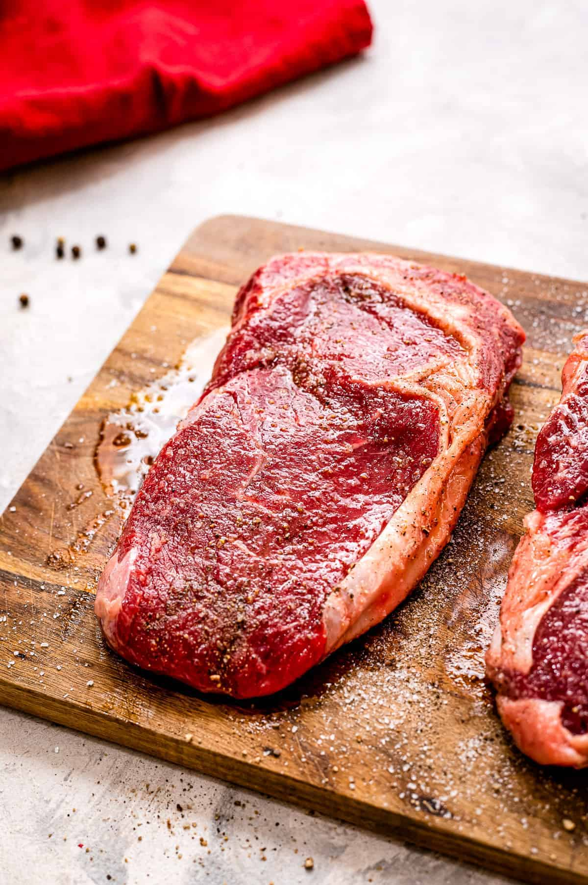 Wood cutting board with raw steak seasoned with salt and pepper