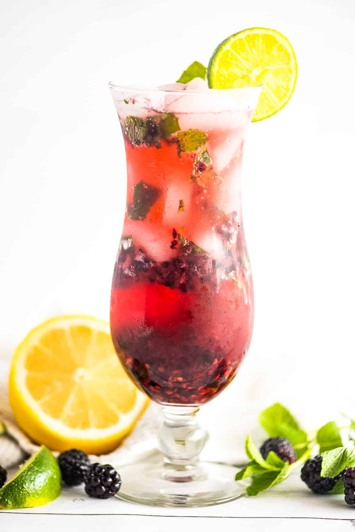 A tall glass with a blackberry mojito garnish with lime