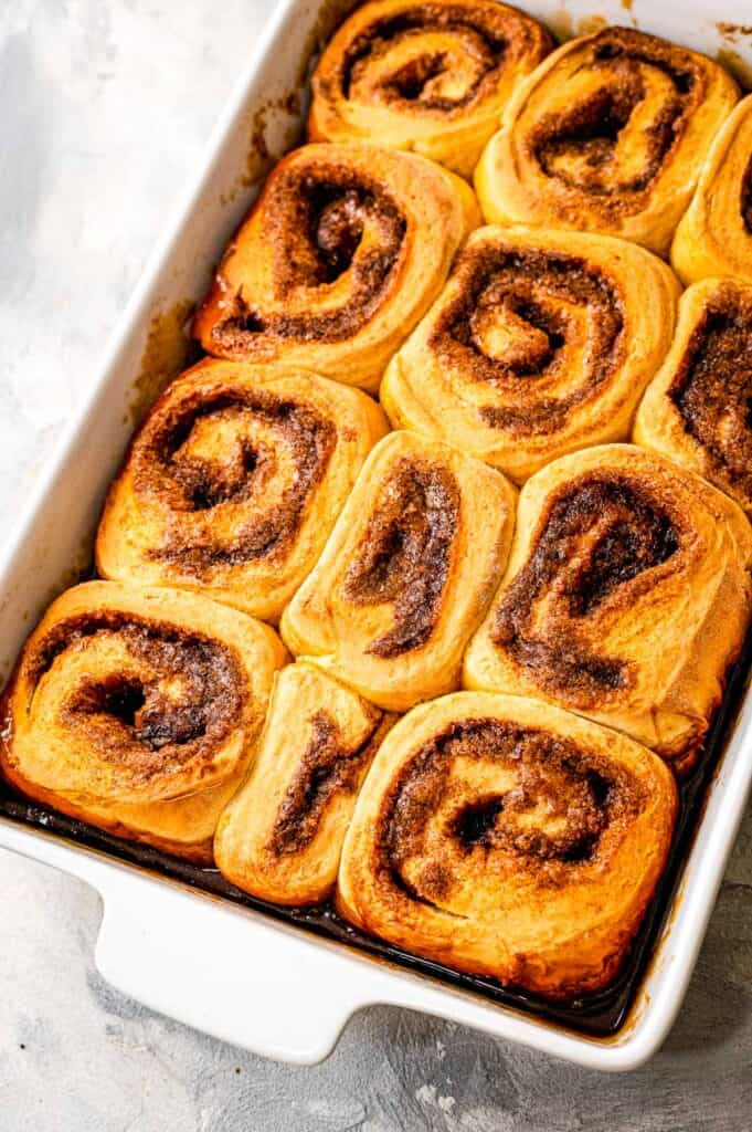White baking dish with baked caramel rolls in it