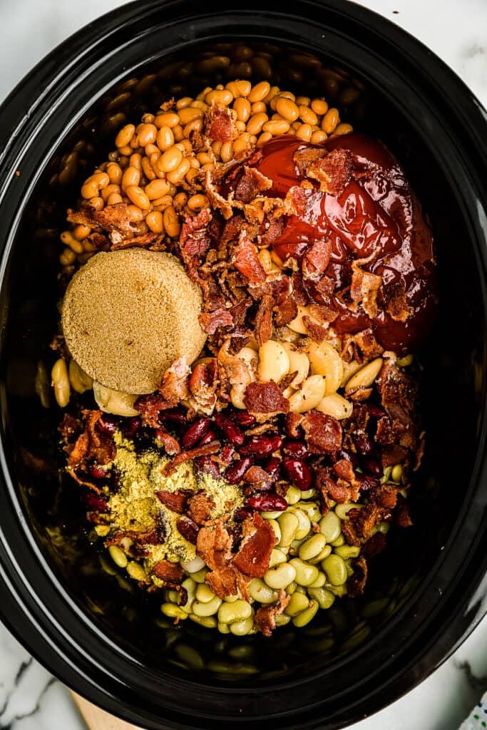 Overhead image of sauce, brown sugar plus beans in crock pot