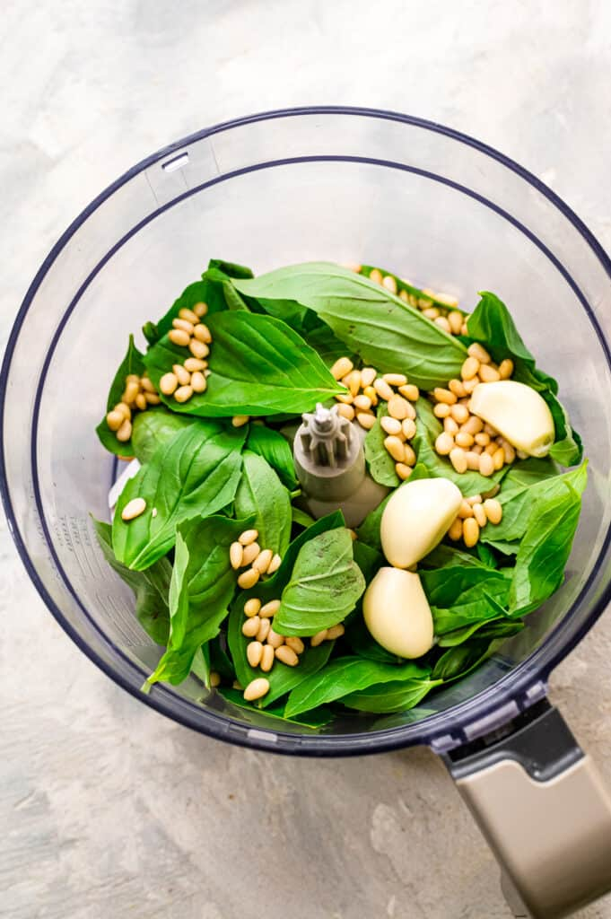 Food processor with ingredients for fresh pesto