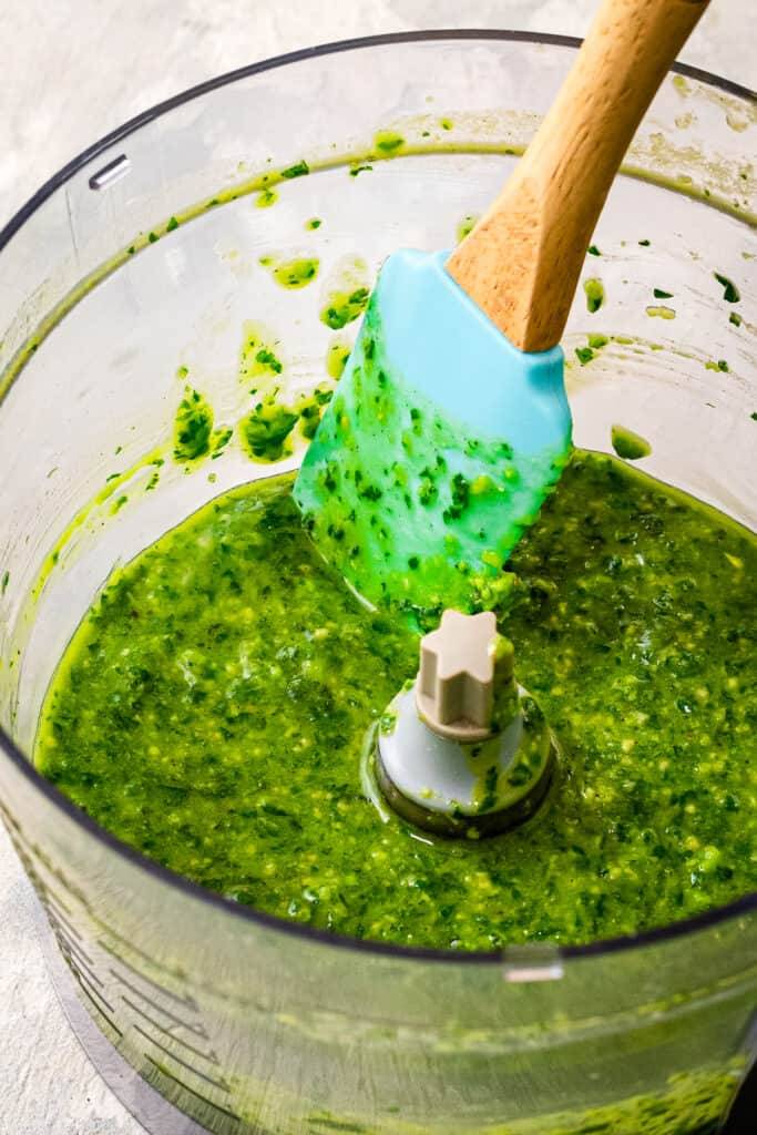 A food processor with pesto in it and spatula stirring it