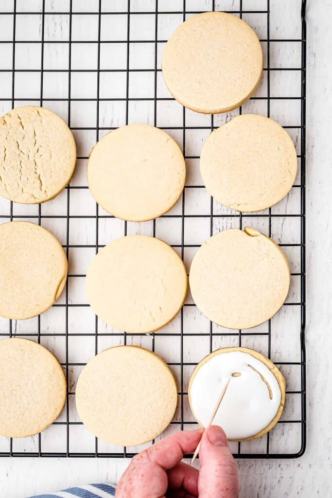 Sugar Cookie spreading royal icing out with toothpick