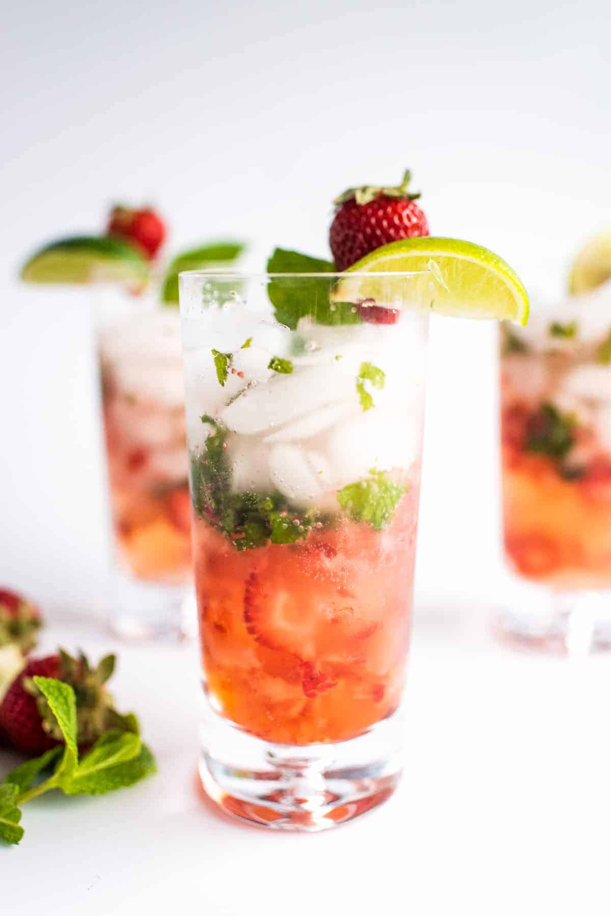 Tall glass with strawberry  mojito garnished with lime and strawberry