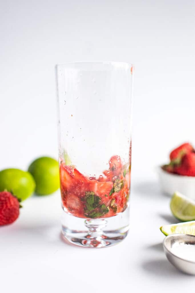 Muddled ingredients in glass for strawberry mojito