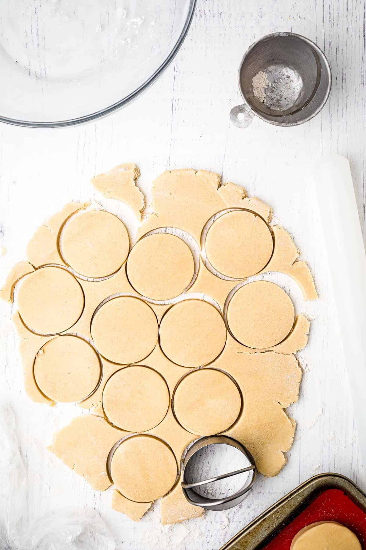 Round cookie cutter cutting out of sugar cookie dough