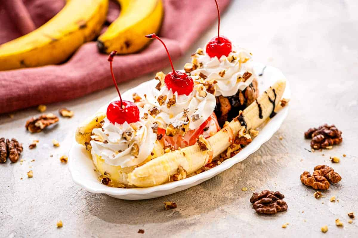 White serving dish with a banana split in it