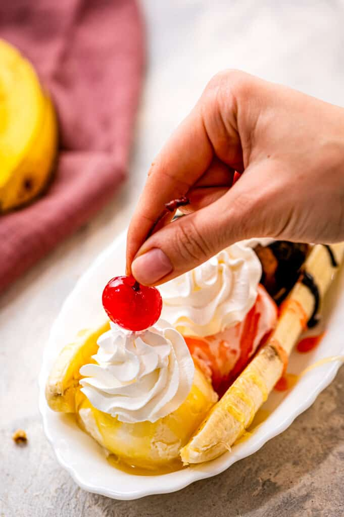 Placing a maraschino cherry on top of whipped cream