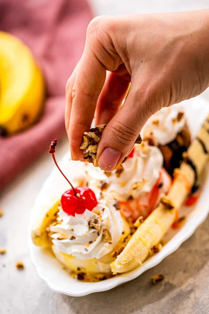 Hand sprinkling chopped walnuts on banana split