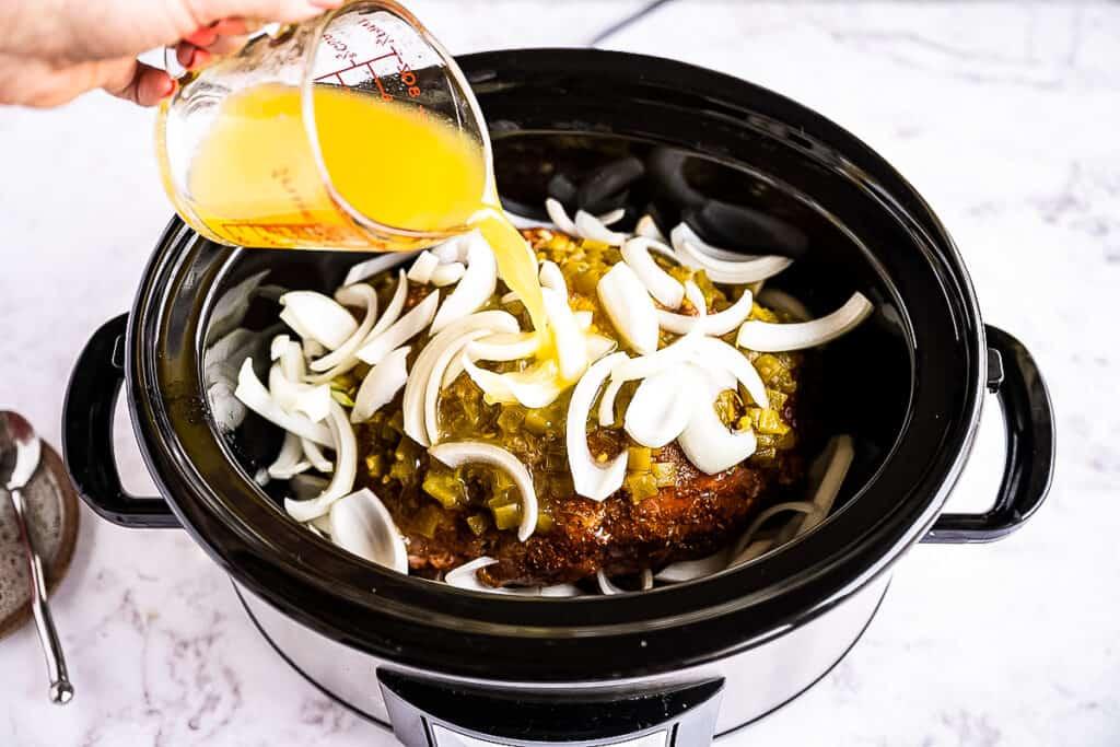 Pouring citrus juices into crock pot for carnitas