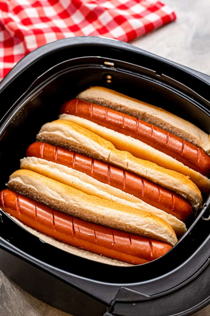 Air Fryer basket with hot dogs inside of buns