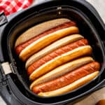Overhead image of hot dogs in buns in an air fryer basket