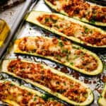 Overhead image of stuffed zucchini boats on foil lined baking sheet