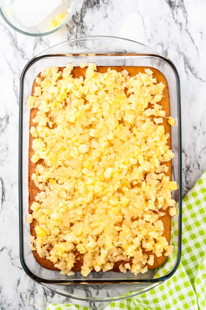 Overhead image of baked cake with crushed pineapple on top