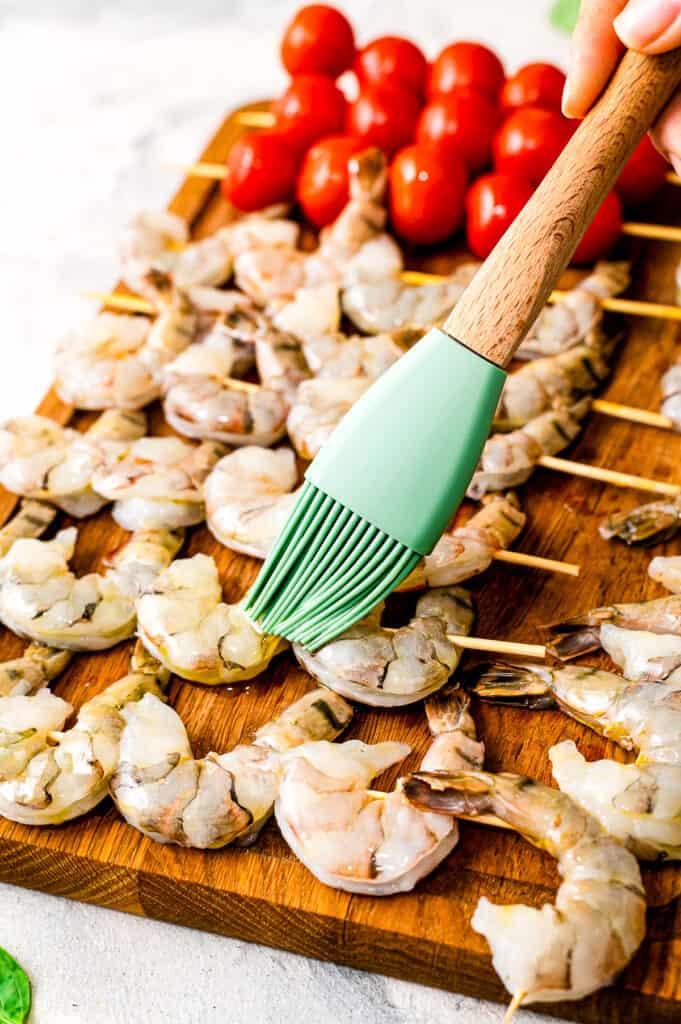Basting brush putting olive oil in shrimp skewer