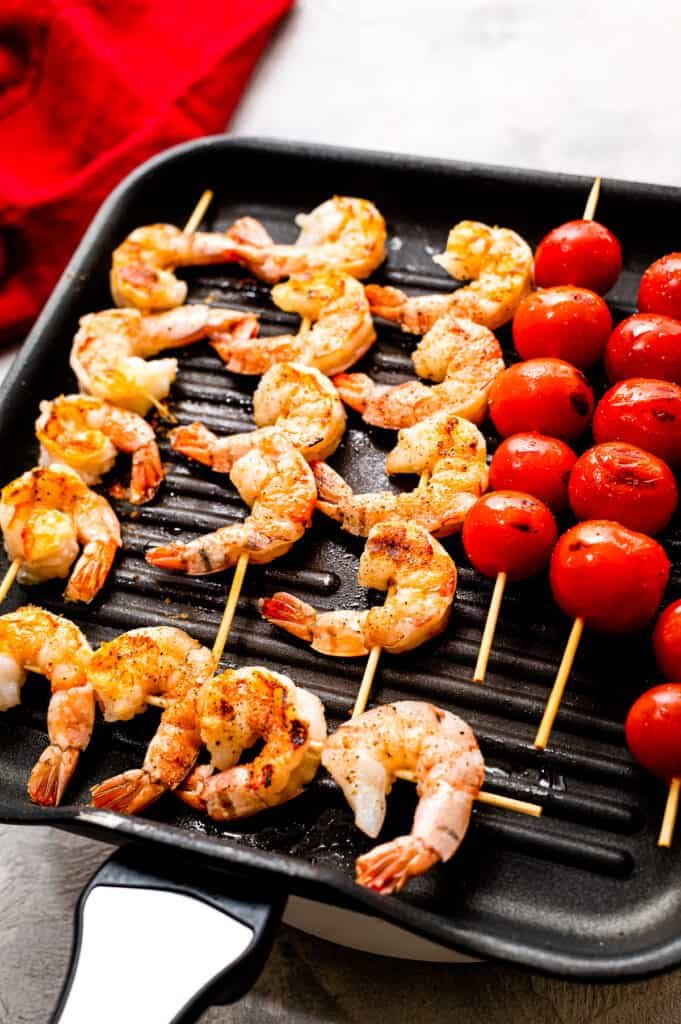 Grill pan with skewers of shrimp and cherry tomatoes