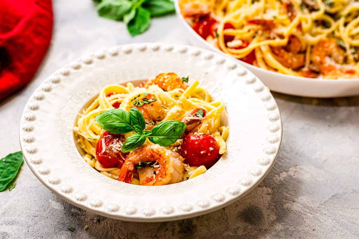 White bowl with shrimp pasta in it