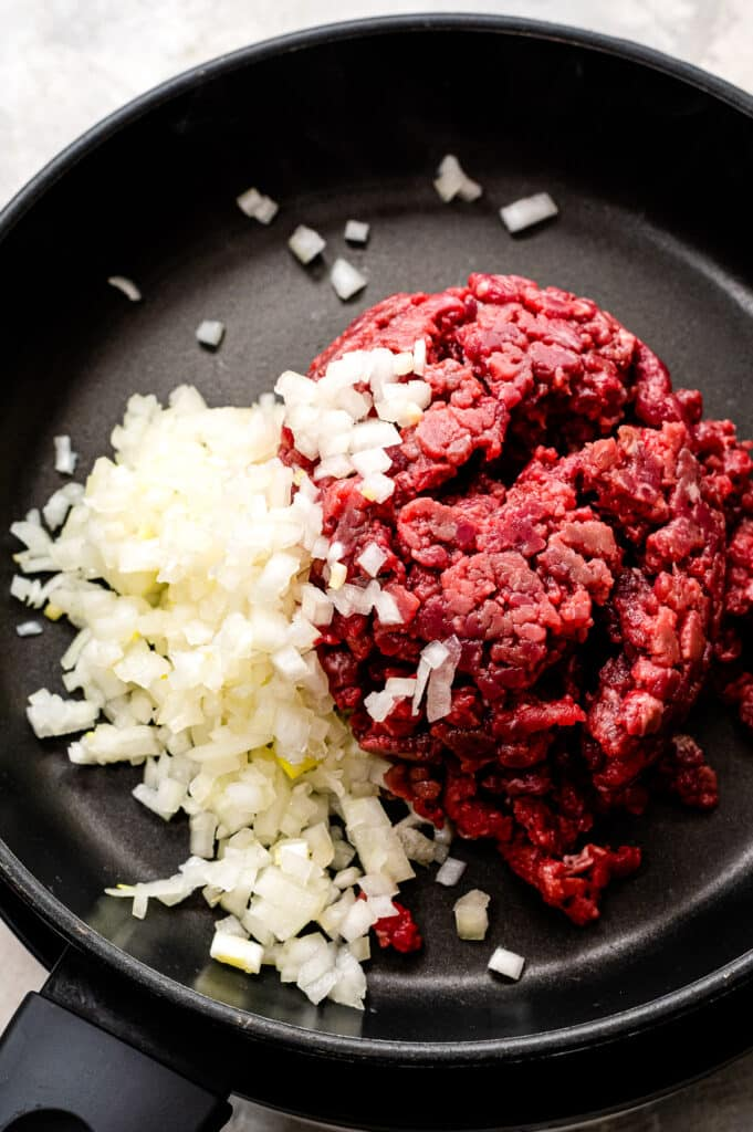 Skillet with onions and ground beef before cooking