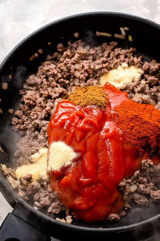 Skillet with ground beef, tomato sauce and seasonings