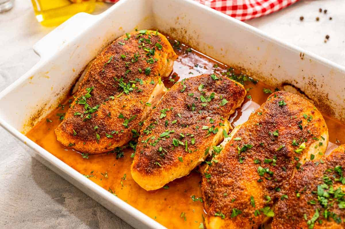 White baking dish with seasoned and baked chicken breasts