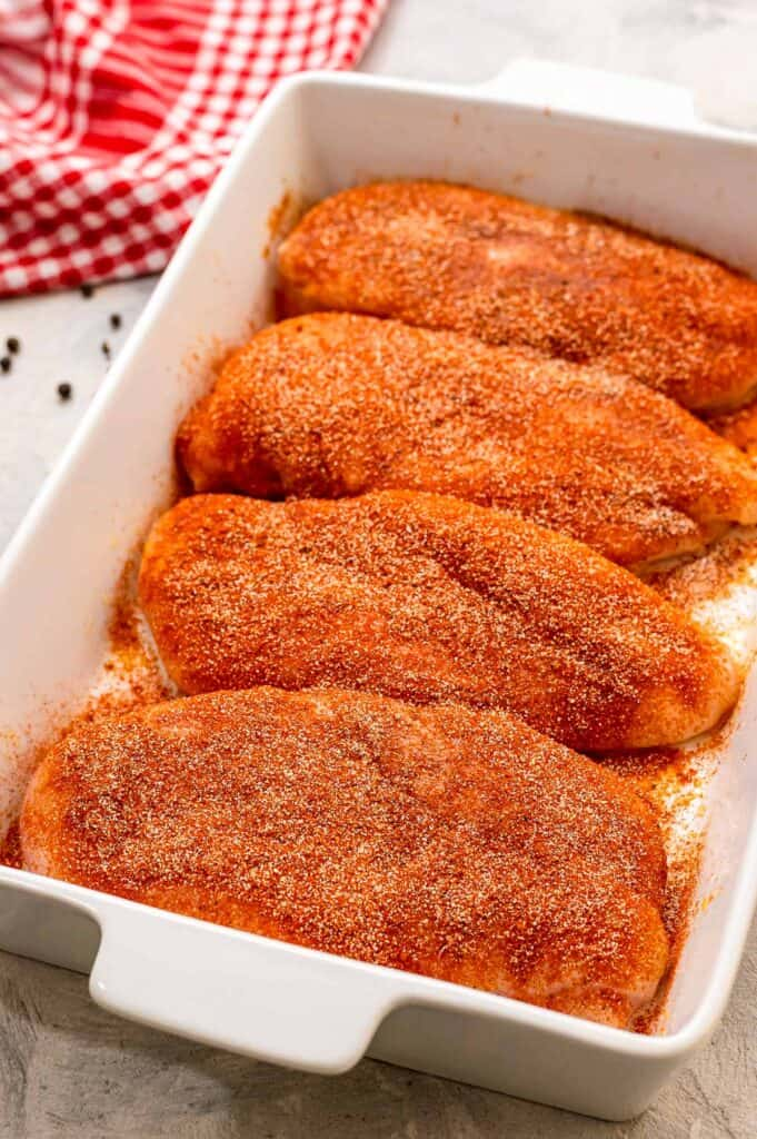 White baking dish with seasoned chicken breasts in it