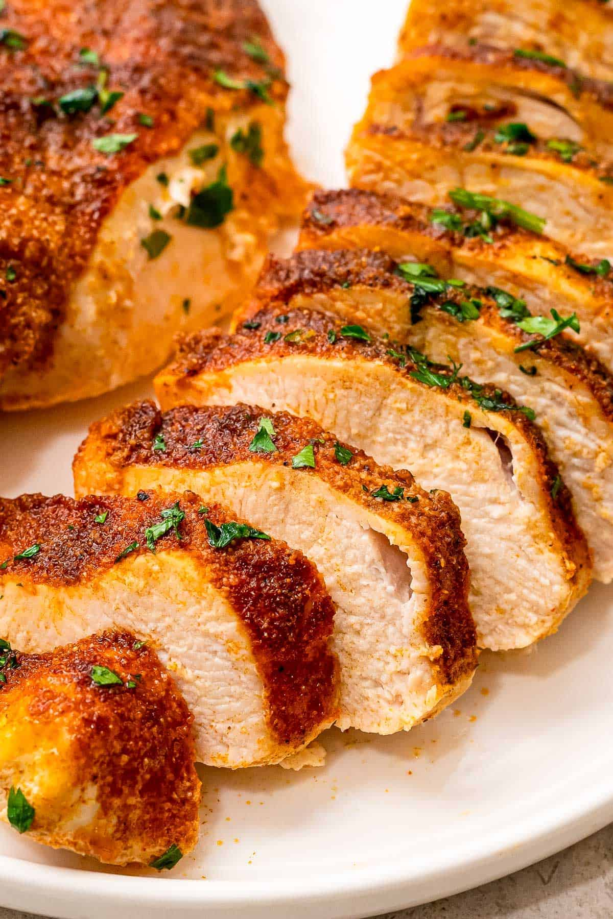 Sliced chicken breasts with seasoning on it