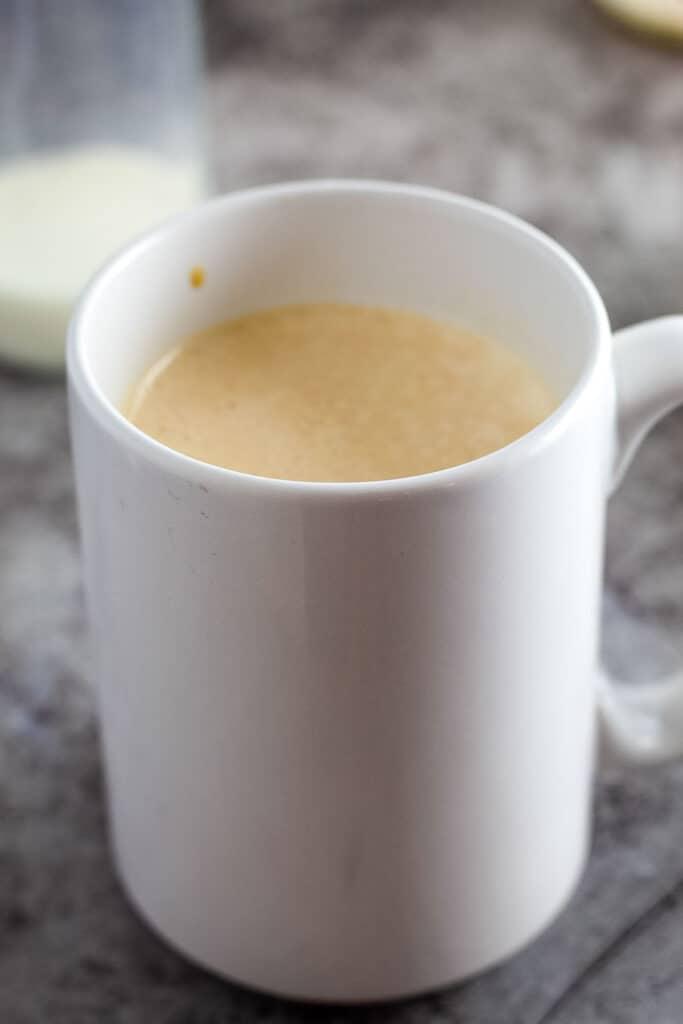 White coffee mug with sweetened coffee in it
