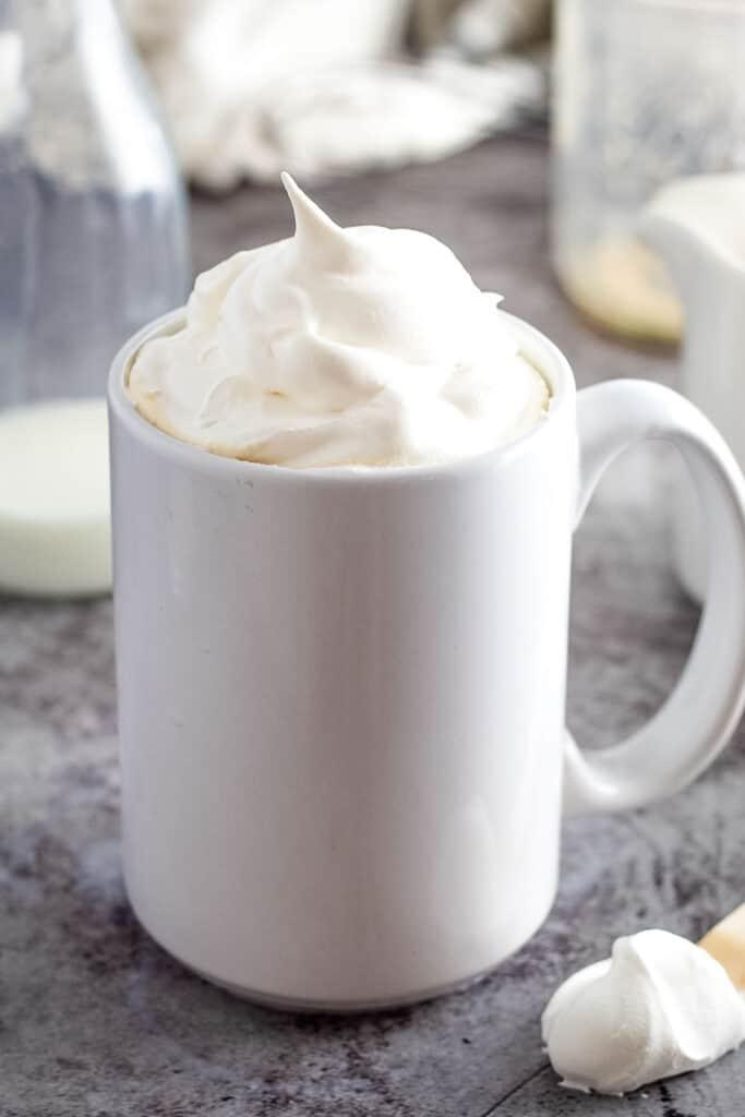White coffee mug with whipped cream on top