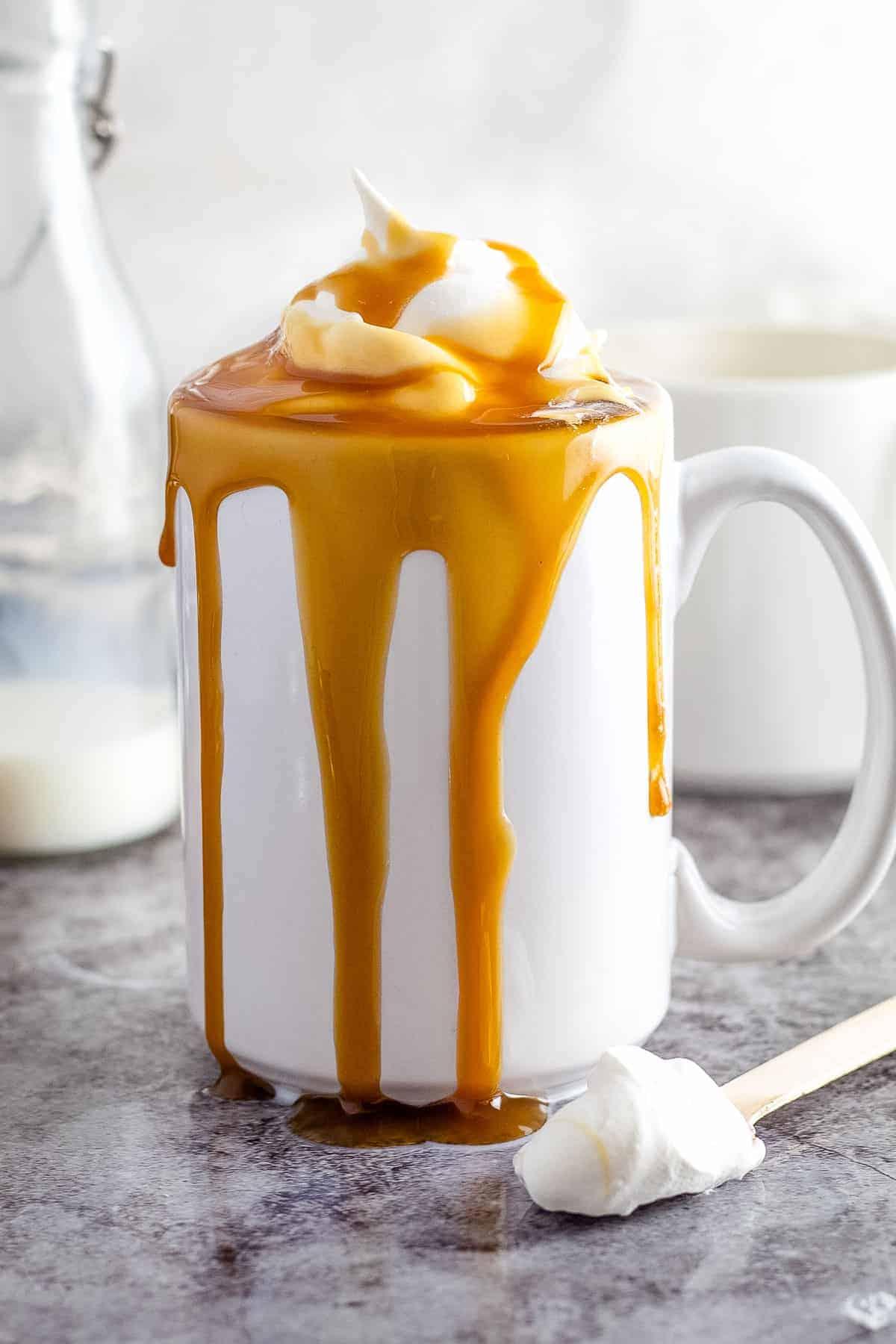 Caramel Macchiato in white mug on gray background