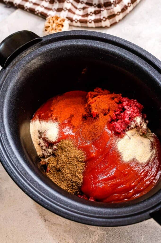 Black crock pot with ground beef, tomato sauce and spices